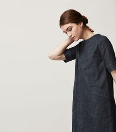 A-line dress with two deep patch pockets in washed, indigo-dyed denim. Lightly fitted at the top and across the shoulders, flaring into a full A-line shape through the body. Exposed metal zip at back with puller. Deep hem detailing.