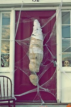 DIY Spider Cocooned Body. Two trash bags filled with leaves, using tape to shape. Covered in cheesecloth, and tea stained twine.