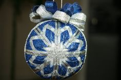 "Robyn and Annie of YouniqueOrnaments say:  Featuring glittering blue ribbon layered with sheer ribbon of white and silver, this stunning handmade ornament is topped with bows of silver and blue. Sure to be loved by the collector on your list!    Each approximately 3"" ornament is uniquely packaged with our signature colors including a dated name card. Purchase more than one ornament from our shop and all additional ornaments ship free!"