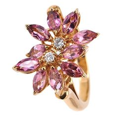 Asprey Yellow Gold Diamond Pink Topaz Daisy Ring. Asprey's iconic Daisy Collection presents an 18K yellow gold ring featuring two overlapping daisies.The flowers are comprised of marquise-shaped pink topaz and each flower has a center prong-set diamond. 21st century