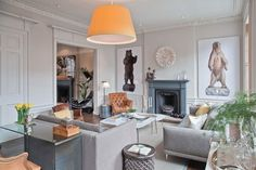 "Most walls in this Edinburgh apartment, renovated by New York–based architect and interior designer Juan Carretero, are painted Farrow & Ball's Cornforth White, a warm gray, but the designer was adamant about adding flourishes of color. ""He was very persuasive about the huge yellow lampshade,"" says the husband. ""He believed this would represent the sun that he didn't think we saw enough of in rainy Scotland—which is not true, of course!"" The bear photographs—a perpetual conversation…"