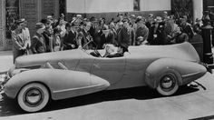 1937: British born actor Cary Grant (1904-1986), and American actress Constance Bennett (1904-1965), stars of the film 'Topper' directed by Norman Z McLeod, ignore the crowd gathered around them as they drive in the Topper Buick.