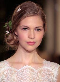 Bridal Show in New York: Der seitliche Haar-Knoten bekommt blumige Unterstützung. Das Make-up wurde in zarten Rosé und Pink-Tönen gehalten. Verantworlich für den romantischen Look bei der Show von Designerin Carolina Herrera, waren die Visagisten von Bobbi Brown.