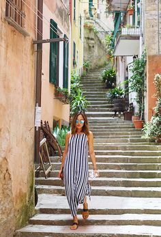Aimee Song wears a striped maxi dress, slide sandals, and mirrored sunglasses