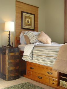 Turn a trunk on its side for a nightstand and hang a bamboo window treatment to act as a headboard.