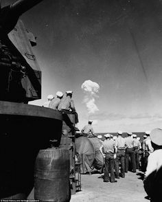 6 of 9 The newly declassified images show the World War II aircraft carrier which was one of nearly a hundred ships used as targets in the first tests of the atomic bomb at Bikini Atoll in 1946. Here, Sailors watch the 'Able Test' burst miles out to sea from the deck of the support ship USS Fall River on 1 July 1946.