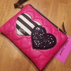 "Betsey Johnson ""Double the Love"" wristlet Brand new with tags. Betsey Johnson ""Double the  Love"" wristlet. Vibrant fuchsia base with the signature hearts on the front, one black and white striped and the other black sequined. Back is all fuschia. Removable wrist strap. Zippered top. Measures 8.5 x 6. Betsey Johnson Bags Clutches & Wristlets"