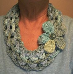 Cindy Lewis Robinson - Ta-dah Neck-Laces Icord and loom knitted into a cowl, with a flower added for flair. Sugar and Cream in Country Stripes for the scarf and flower. She states that it took less than one and a half. 3 pegs to make the icord and then ewrapped it on the 40 peg round loom. Knit over by finger. No pattern. It was about 15 rows but curls under. She states it took about 8 hours to make. Cindy Lewis Robinson's photo (Facebook photo from the Loom Knitting group)