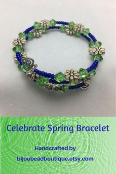 Celebrate Spring Green and Blue Wire Wrap Bracelet. This 2 coil, beaded, memory wire bracelet is composed of faceted green glass beads, royal blue seed beads, and silver metal flower beads. The bracelet sports two dainty, silver metal, Celtic-style heart charms.