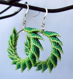 "Three shades of green, give this pair of earrings a ""reptilian"" feel. Twenty eight individually hand-woven, Delica glass bead, ""spike"" like petals, stitched to silver loops make up these bold statement earrings."