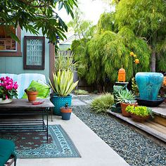 Chic backyard on a shoestring: A brilliant color palette transforms this patio and raised deck into an inviting space for relaxing and entertaining. A perfect mix of ceramics, textiles and lush plantings—all great outdoor living room design ideas.