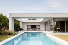 A concrete canopy shelters this pool house by Steven Vandenborre