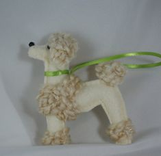 This handsome fella is a cream felt poodle ornament. He is made from craft felt and novelty yarn. He has glass bead eyes and nose and is sporting a green satin collar. He measures 3 long and 4 tall. (Each ornament may vary slightly and the collar and hanging string color may vary.)  As an owner of several rescued standard poodles, I love everything poodle! Growing up, we had felt ornaments on our Christmas tree that my grandmother had made. Several years ago, I began making felt ornaments…