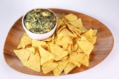 the chew | Recipe | Clinton Kelly's Spinach Artichoke Dip     	     1/3 cup Mayonnaise     1/3 cup Cream Cheese     1/4 cup Sour Cream     1 cup freshly grated Parmesan Cheese     1 cup chopped Marinated Artichokes (drained and rinsed)     2 cups chopped Frozen Spinach (thawed and drained)     2 tablespoons Roasted Garlic     Salt     freshly cracked Black Pepper     fresh Tortilla Chips (to serve)