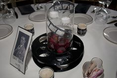 My centerpieces for 1920s themed wedding - Films - glass candle holder (from Pat Catan's) with a filmstrip cutting and flower inside on top of a movie real.