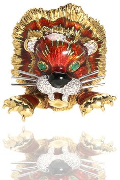 An enamel and diamond lion brooch with emerald eyes, Kutchinsky, London;  signed Kutchinsky; with London hallmark; gross weight approximately: 54.5 grams; mounted in eighteen karat gold; length: 1...