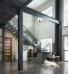 This home features an open concept entry way that gives sight lines to the concrete floating stairs, living room, kitchen and dining room. The steel beams are exposed throughout the home. Entry way custom staircase Bridgewater Innovative Builders b Livibg Room, Staircase Interior Design, Stairs In Living Room, Warehouse Design, Concrete Stairs, Kitchen Living, Room Kitchen, Steel Beams, Floating Stairs