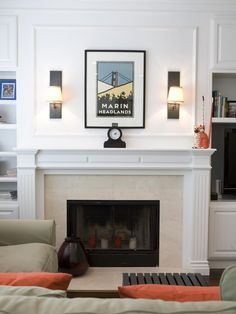 Across from an oversized gray plush sofa sits a white marble fireplace, the mantel of which is used to display a small clock and two decorative cat statues. Above the mantel hangs a framed print of the Marin Headlands and two wall sconces.