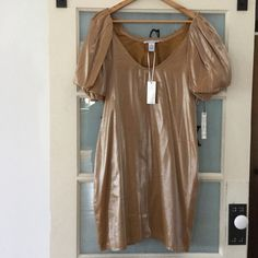 """VERTIGO PARIS Metallic Knee Dress SZ XL - NWT! This is a vertigo Paris knee-length cocktail dress with a metallic finish. The sleeves are puffy with elastic closures. The neckline is rounded and deep. It is fully lined. Left side zipper under arm.  Darted bust. It is made of nylon and Rayon. It has never been worn. LENGTH: 36"""" BUST: 42"""" WAIST: 38"""" Vertigo Paris Dresses"""