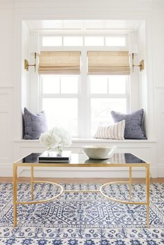 Love seat in window with pillows and coffee table