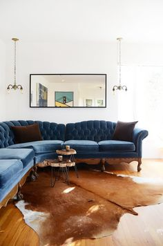 Navy tufted sofa with brown pillows, cow hide rug, and hanging light fixtures