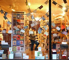 Fall 2010 window display: Postcards on ribbon strewn across the windows like garland.