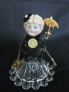 Crystal assemblage doll.  Antique blond porcelain head, crystal bowl and candlestick body, steampunk key arms holding fan and umbrella.