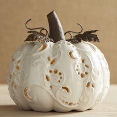 Keep your fall decor nice and neutral with our exclusive glazed porcelain pumpkin. Crafted by hand and accented with wrought iron, it casts an intriguing glow by way of a flickering tealight.