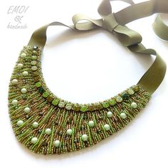 """Spring grass"" statement necklace by Emoi Handmade studio. Multilayered beaded lines remind of fresh grass blades, with specks of pearl and crystal dew. The necklace has a very beautiful shape, which lengthens the neck. Color: green, light green, peach, olive green. Technique: bead embroidery on felt. Size: Central part width 16 cm, height 6 cm, ribbon length 55 cm."