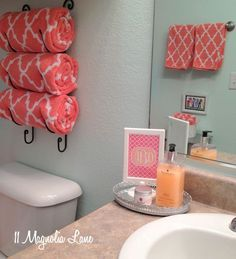 Coral and aqua is an unexpected color combination that works well in a girls bathroom and transitions from little girl, to tween, to teenager. The bright and cheerful trellis/ quatrefoil towels are from Home Goods and are stored rolled up in a repurposed wine rack. A matching monogram print and colorful hand soap complete the decor.