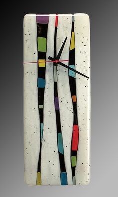 Fragments - Vertical Wall Clock by Nina Cambron. Add a splash of personality to your wall with the exuberance of fused glass. Undulating bands of French vanilla alternate with strips of colorful glass shards and black frit. Signed on front. Ready to hang. Uses one AA battery (included).