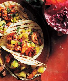 A homemade chili paste is easy to make—garlic, olive oil, chili powder, cumin, oregano, salt, and pepper—but delivers a bold, smoky taste that pairs beautifully with a sweet-and-spicy pineapple-jalapeno salsa. Grill the tortillas before filling to add char and make them more pliable.