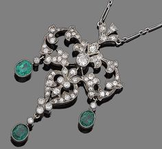 A belle époque emerald and diamond pendant necklace, circa 1900  The openwork cartouche of highly stylised foliate design, millegrain-set throughout with old brilliant-cut and cushion-shaped diamonds, suspending three oval-cut emerald drops, to a fetter-link chain, diamonds approx. 1.55cts total, lengths: pendant 6.0cm, chain 49.2cm