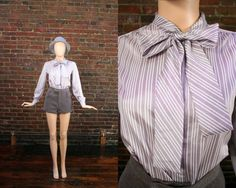 Vintage Pussy Bow Blouse Bowtie Ascot Top Lavander Striped Secretary Shirt (M)    A lovely little bow tie blouse. Pretty candy stripes in lavender and white. • 1980s  • pastel purple and white • Polyester • Tie ascot • Buttons in the front • Buttons at cuffs • Lightweight • Clipped back on mannequin • Labeled a size 10 • Fits like a Medium • Ships Worldwide  • One of a kind - Only one in stock    Length: 23 inches | 58 cm  Bust: 37 inches | 94 cm  Waist: 35 inches | 89 cm Condition notes…