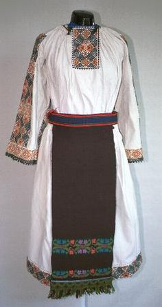 Women's costume from county of Bistriţa-Năsăud; Gathered neck linen chemise (cămaşă încreţită) with open ended sleeves. It has dense embroidery on the sleeves in brown and black geometric patterns (tablă),  and a square inset at the neck decorated with the same embroidery. A narrow row of black crochet lace is attached to the sleeve hem