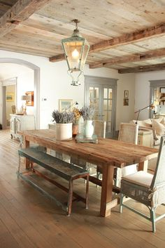 rustic provence kitchen with wood beam ceiling, wood floors, a cool table/bench/chair combo and carriage house light fixture idea.