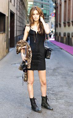 vestido negro estilo corsé, chaqueta de print de leopardo y botas planas estilo motero