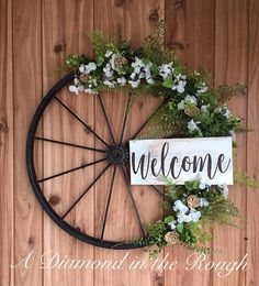 Wagon Wheel Welcome Wreath - what a perfect way to welcome guests to your rustic/farmhouse home. :) I just love this idea!!!! #wagonwheel #wreath #frontporch #frontdoor #rustic #rusticdecor #farmhouse #welcome #affiliate