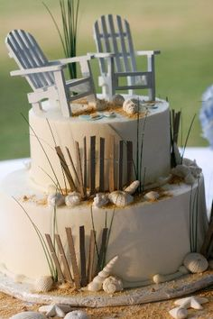 A beach cake with all the bells and whistles. Sand, shells, dune fence, dune grass and Adirondack beach chairs.