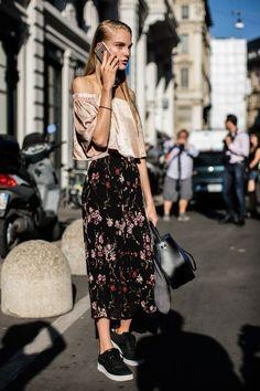 9 Maneiras imperdíveis de usar tênis na balada. Top cropped rosa com decote ombro a ombro, saia longa preta com estampa floral, tênis preto