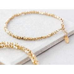 Sparkling gold plated faceted single strand bracelet. Geometric silver nuggets plated in gold coil around your wrist in this simple, modern bracelet.