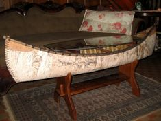 """This handsome birch bark canoe coffee table will add a lake feel to any home, lodge or cabin.    Birch Bark Canoe with solid cherry base and glass topExclusive Cottage Surroundings Design  60""""L x 16""""W x 19""""H"""