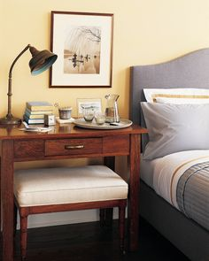 If space allows, a desk is an excellent choice beside the bed. Its large surface area is convenient for files or correspondence and leaves room for luxuries, such as a drink tray. The gooseneck lamp can be pointed toward the work surface or the bed. The bench slides underneath, out of the way, when not in use.