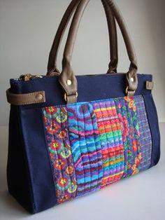 Bolsa feita de lona e a frente com tecido de algodão quiltada. Possui duas divisões com fechamento de zíper e o centro com fechamento de botão de imã. Alça de ombro feita de couro ecológico.