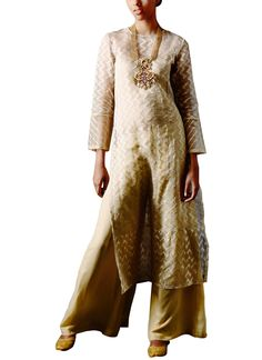 Anita Dongre brings to you a golden brocade long kurta with palazzo pants that is trendy, contemporary, yet exudes an Indian appeal. The fluidic kurta features full sleeves, long side slits and a high neck with all-over chevron prints in hues of gold. It is teamed with palazzo pants that give the outfit a relaxed feel. Wear it with a pair of mojris, statement jewellery and a sling bag for a truly alluring look.