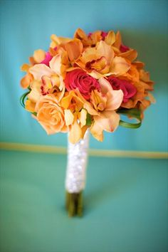 Turn up the heat. Hot accents toned down with apricot colored cymbidiums.