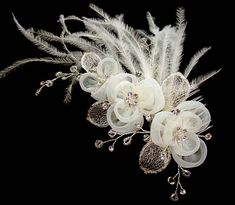 Fascinator with organza flowers and soft ostrich feathers embellished with crystals, beads and silver mesh leaves. Approx. 14x7cm plus feathers $69.00