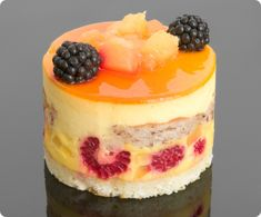 Petit Four with a base of what appears to be raspberry clafoutis, topped with pastry cream, fruit glaze, and fresh blackberries.