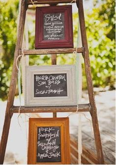 an old ladder and some chalkboard frames