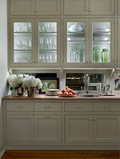 Traditional butler's pantry features glass-front upper cabinets lined with glass shelves lit by ...